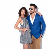 side view of an embraced modern couple looking to side on white studio background poster