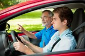 stock photo of driving  - Teenager learning to drive with his driving instructor - JPG