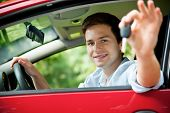 stock photo of car key  - teenager sitting in new car and shows the keys