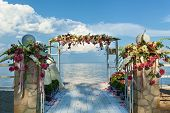 Beautiful Wedding On The Beach. View Of The Sea. The Wedding Place Is Decorated With Bouquets Of Flo poster