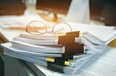 Glasses Placed On Unfinished Documents Stacks Of Paper Files On Computer Desk For Report , Piles Of  poster