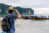 Young Man Traveler With Green Backpack And Hat Looking At The Sea With Long Boat Thailand Background poster