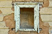 stock photo of oddities  - Empty wooden window frame and chipped wall texture - JPG
