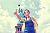 Statue of Liberty New York City tourist woman happy doing thumbs up. Asian girl on summer vacation t poster