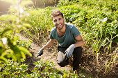 Young Cheerful Attractive Bearded Male Gardener In Blue T-shirt And Black Sport Pants Smiling, Worki poster