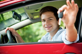 stock photo of driving school  - teenager sitting in new car and shows the keys