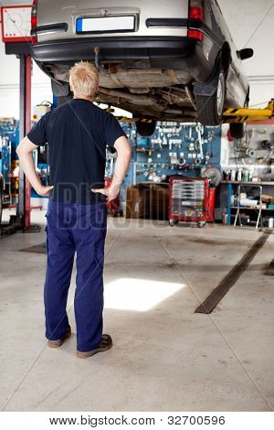 A young mechanic looking at a car that needs repair