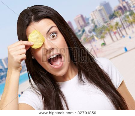 portrait of young woman holding potato chip in front of her eye against a coastline