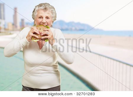 senior woman biting a healthy sandwich near the beach