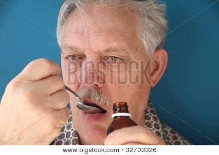 sick older man takes liquid medicine