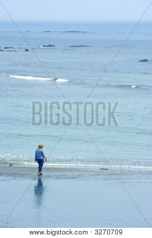 Old Woman Alone On The Beach