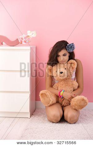 ziemlich junges Mädchen kniend am Boden, umarmt von Teddy Bear in Rosa Zimmer.