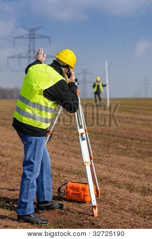 Land surveyors measuring land with theodolite speaking through transmitter