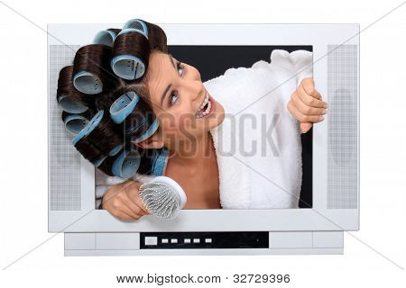 Woman popping out the TV with hairroller on.