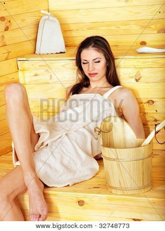 Young woman in sauna. Overheating danger.