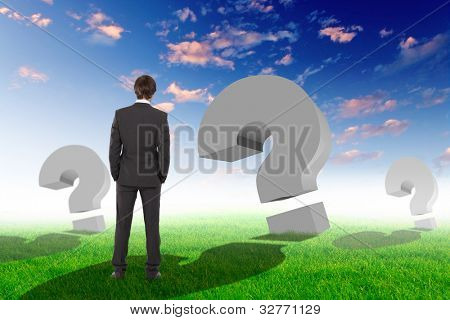 Businessman standing outside with question marks around him