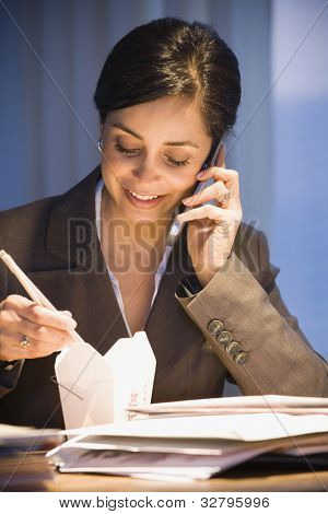 Hispanic businesswoman eating take out food