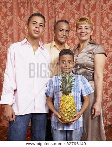 Hispanic family holding pineapple