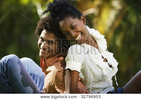 South American couple sitting back to back