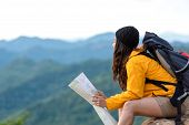 Asian Women Hiker Or Traveler With Backpack Adventure Holding Map To Find Directions And Sitting Rel poster