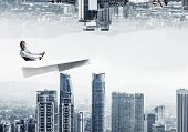 Businessman Flying In Paper Plane. Two Modern Urban Worlds Located Upside Down To Each Other. Funny  poster