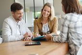 Couple meeting real-estate agent in office poster