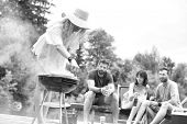 Black and white photo of Woman preparing food in barbecue grill with friends on pier poster