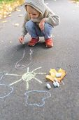 Little Boy 3-5 Years Old, Draws With Colorful Crayons On Asphalt, In Summer In Fall In A City Park.  poster