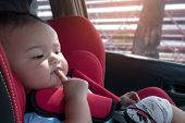 Asian Baby Girl Enjoy Sitting On Car Safety Seat During Drive. One Girl Sit In Safety Seat With Prop poster
