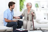 stock photo of medical exam  - Young man taking the blood pressure of an older lady - JPG