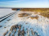 Beautiful Aerial View Of Snow Covered Fields With A Two-lane Road Among Trees. Rime Ice And Hoar Fro poster