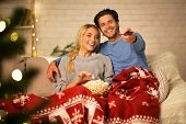 Christmas Eve. Loving Couple Watching Tv And Eating Popcorn At Home, Covered With Blanket poster