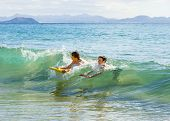 stock photo of papagayo  - boys have fun riding in the waves - JPG