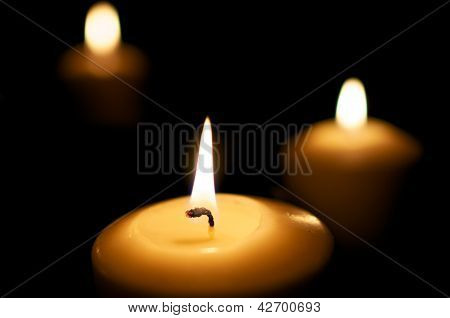 Three candles burn in the night