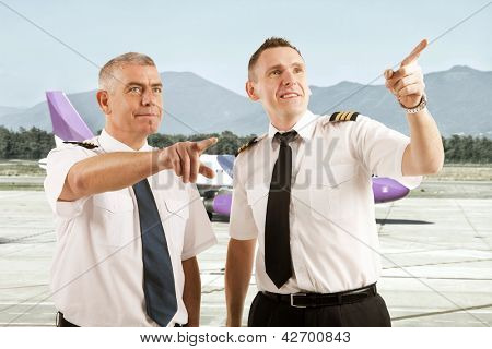 Cheerful two airline pilots wearing uniform with epaulettes standing on airstrip and pointing at something with airplane in the background