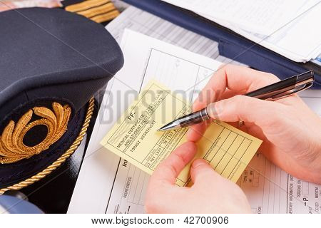 Close up of an airplane pilot hand holding medical certificate with equipment including hat, epaulettes and other documents in background