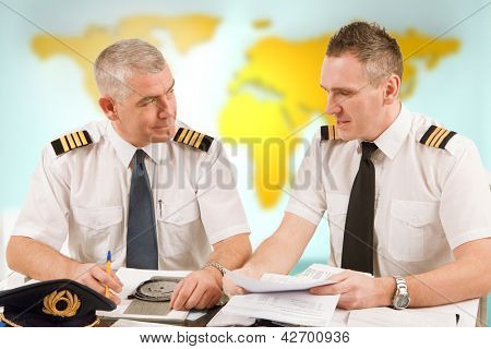 Two airline pilots preparing to flight, checking papers flight plan, log book. Pilots are sitting in AIS ARO Air Traffic Services Reporting Office