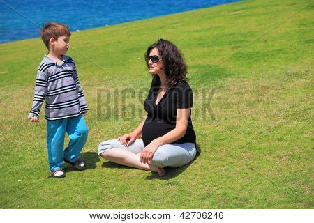 Charming young pregnant woman rests with lovely four-year-old son on the grass near the sea