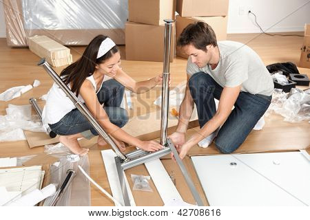 Couple moving in together assembling furniture table. Young interracial couple in new house or apartment home working together to assemble table. Asian woman, Caucasian man.