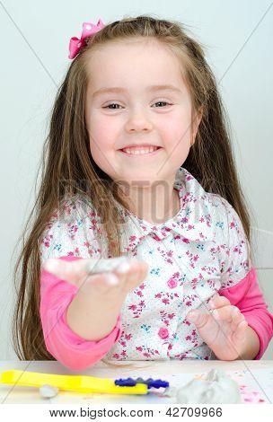 Linda chica sonriente esculpir usando arcilla