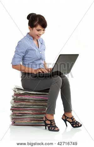 Woman Working With Laptop And Sitting On Stack Of Paperworks