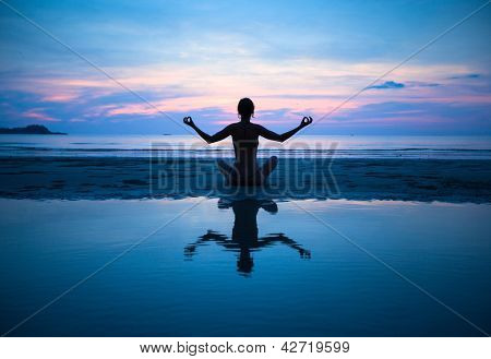 Woman practicing yoga on the beach at sunset (with reflection in water)