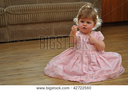 Small Girl In Pink Dress Couriosly Looking At Her Hand