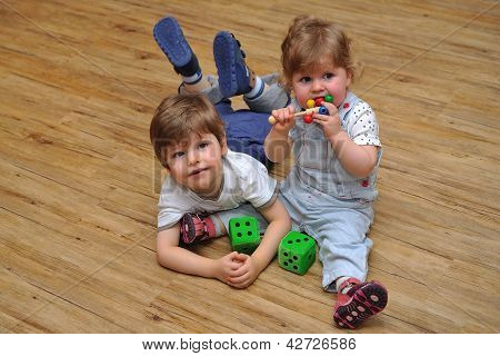 Curious Siblings Sitting And Lying On Wooden Floor