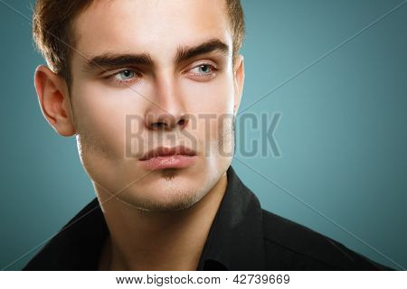 Trendy young man in black shirt, portrait of sexy fashion boy looking right over dark blue background