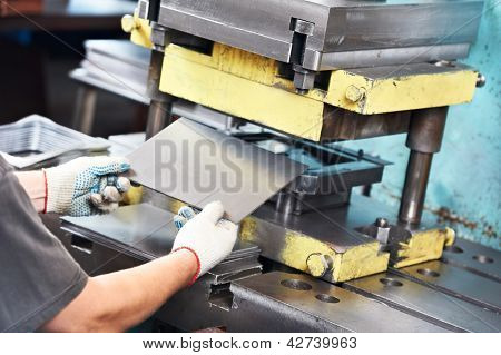 worker at manufacture workshop operating metal press machine