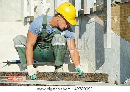 mason worker tiler making stairway from granite stone tile blocks
