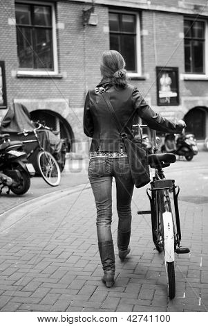 Woman Walking Bike On The Sidewalk