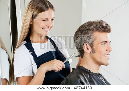 Happy female hairdresser cutting customer's hair at salon