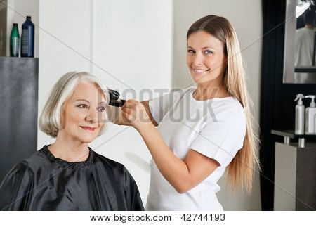 Portrait of female hairdresser with straightener ironing customer's hair at salon